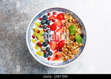 Frühstück smoothie Schüssel mit Obst und Müsli. Superfood Schüssel auf konkreten Hintergrund isoliert. Sauber, Essen, Diät, Gewichtsverlust Konzept - Stockfoto