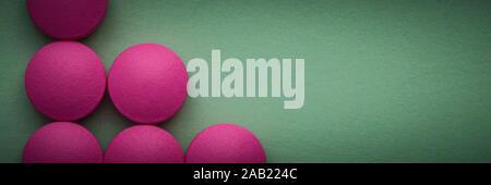 Rosa Pillen auf grünem Hintergrund - Stockfoto