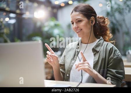 Porträt der moderne junge Frau, Musik hören und tanzen, während mit Laptop auf der Terrasse im Cafe, kopieren Raum