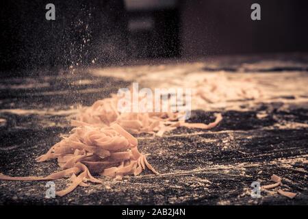 Home frische rohe Nudeln auf dem Küchentisch schwarzen Beton, mit Mehl bestäuben. - Stockfoto
