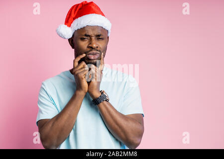 Nachdenklich dunkelhäutigen Mann mit Stoppeln in Santa hat halten die Hände auf Stellen, zu versuchen, die Entscheidung zu treffen, oder etwas Wichtiges erinnern, denken Isolat - Stockfoto