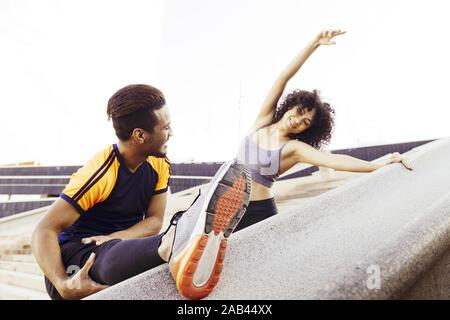 Glückliche junge Mann und Frau stretching auf Stadt Treppen vor dem Ausführen, Fitness, urbane Sportarten Workout und gesunden Lebensstil Konzept, kopieren Platz für Text