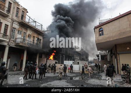Bagdad, Irak. 25 Nov, 2019. Rauchwolken steigen als Objekte brennen Während der gewalttätigen Auseinandersetzungen zwischen Mitgliedern der irakischen Sicherheitskräfte und regierungsfeindlichen Demonstranten auf Al Rasheed Straße. Credit: Ameer Al Mohammedaw/dpa/Alamy leben Nachrichten - Stockfoto