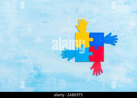 Bunte Rätsel Stück und Hände auf blauem Hintergrund. Welt Autismus Bewußtsein Tag Konzept - Stockfoto