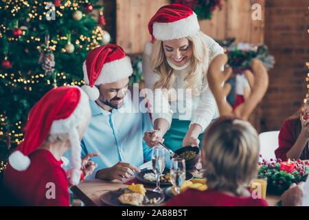 Foto fröhliche, positive nett schön Frau Sorge um ihren Ehemann in santa hut Kopfbedeckung mit ihrem Sohn tragen Geweihe - Stockfoto
