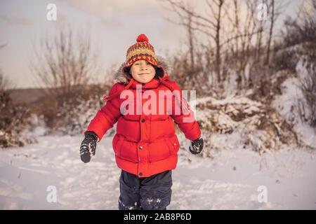 Junge in Rot mode kleidung im Freien spielen. Aktive Freizeit mit Kindern im Winter an kalten Tagen. Junge Spaß mit ersten Schnee. Glückliche kleine Zicklein ist - Stockfoto