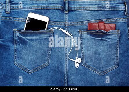 White Smartphone mit Kopfhörern und Leder braun Geldbörse in der Gesäßtasche blaue Jeans, hautnah. - Stockfoto