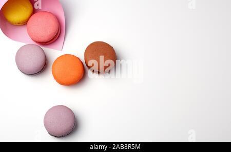 Gebackene macarons in einem rosa Papier Beutel auf einem weißen Hintergrund, aus der Nähe. - Stockfoto