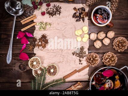 Papier Bündel von braunem Papier und Zutaten für Glühwein auf braunem Holz- Hintergrund, leeren Raum in der Mitte. - Stockfoto