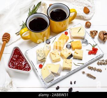 Stück Käse auf ein weißes Holzbrett und zwei gelbe Tassen mit schwarzem Kaffee. Stockfoto