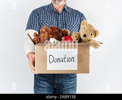 Ein Mann mit einem blauen Hemd und Jeans mit einem großen braunen Karton mit Spielzeug für Kinder, Hilfe für die Armen, weißen Hintergrund. - Stockfoto