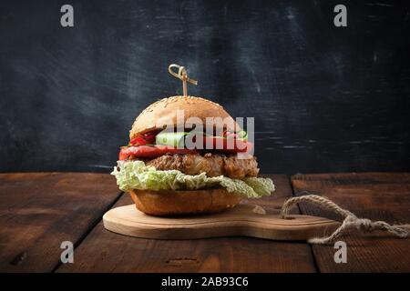 Hamburger mit Schweinefleisch gebratenes Steak, rote Tomaten, frische runde Brötchen Mit Sesam auf einem Vintage Brown Holzbrett. - Stockfoto