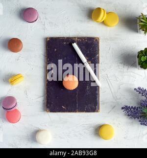 Gebackene runde Macarons, Notebooks, Pen und Pflanzen in einem Topf auf einem weißen Hintergrund, Ansicht von oben. - Stockfoto