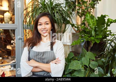 Junge asiatische Frau als Blumenhändler in Ausbildung in Flower Shop