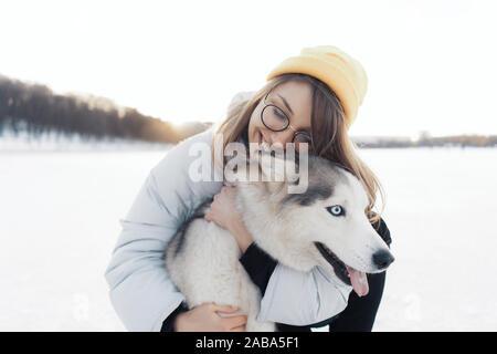 Glückliche junge Mädchen spielen mit sibirischen Husky Hund in Winter Park. Sie gehen auf einem zugefrorenen See
