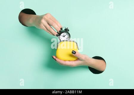 Weibliche Hände halten Wecker und Mappe durch ein Loch auf Neon mint Hintergrund. Zeit ist Geld.