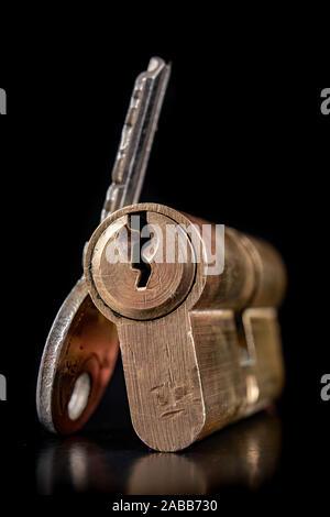Eine alte Tür auf einem dunklen Hintergrund. Ein Patent und Schlüssel die Tür zu sichern. Einen schwarzen Hintergrund. - Stockfoto