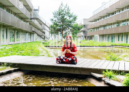 Frau sitzt im Schneidersitz auf eine Brücke mit einer Tasse Kräutertee, Amsterdam, Niederlande - Stockfoto