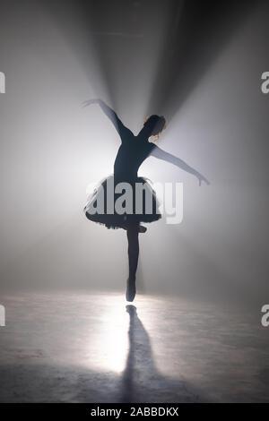 Professionelle ballerina tanzen Ballett in Strahler Rauch auf der großen Bühne. - Stockfoto