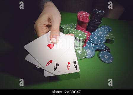 Poker chips auf den Tisch und eine weibliche Hand mit vier Asse schließen oben. - Stockfoto