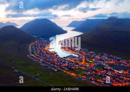 Fantastische Luftaufnahmen abend Stadtbild von klaksvik Stadt mit glühenden Straßen und Fjord, bordoy Island, Färöer, Dänemark. Landschaftsfotografie - Stockfoto