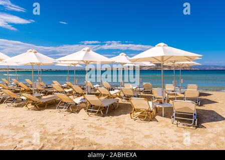 Sonnenschirme und Liegestühle am Strand von Agios Georgios, sehr beliebtes Resort mit feinem goldenen Sand und kristallklarem Wasser. Insel Naxos, Griechenland. V - Stockfoto