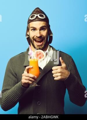 Schöne bärtige aviator Mann mit dem langen Bart auf lächelnde Gesicht holding Glas alkoholfreien Cocktail in Grau in Form gestrickter Pullover mit Hut und Brille auf Blau studio Hintergrund - Stockfoto