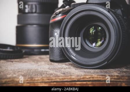 Nahaufnahme von einem schwarzen DSLR-Kamera mit einem 50-mm-SIND 1,8G Prime Objektiv auf einer alten braun Holz- Vintage box Oberfläche. Der Fotograf fotografische Geräte.