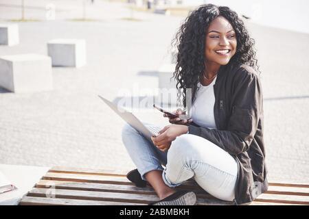 Junge Frau, die auf der Straße arbeiten, die auf Notebook- und Gespräch am Handy - Stockfoto