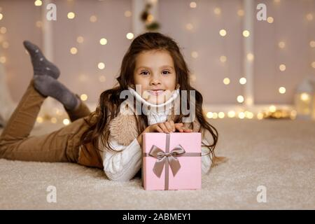 Happy lockiges Kind Mädchen mit Geschenk Box auf dem Boden sitzend auf dem Hintergrund mit Beleuchtung. Frohe Weihnachten. Kopieren Sie Platz - Stockfoto