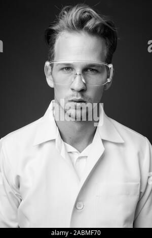 Jungen gutaussehenden Mann Arzt als Wissenschaftler mit Schutzbrille - Stockfoto