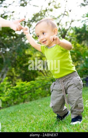 Happy Toddler Boy Laufen lernen im Gras - Stockfoto