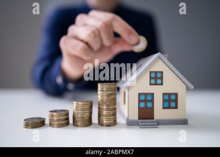 Person's Hand einfügen Münze im Haus Modell mit zunehmender Münzen Stapel auf dem Schreibtisch - Stockfoto