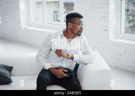 Auf der Suche Was auf außen durch das Fenster zu gehen. Stilvolle afro-amerikanische Kerl in klassischen Verschleiß und Gläser - Stockfoto