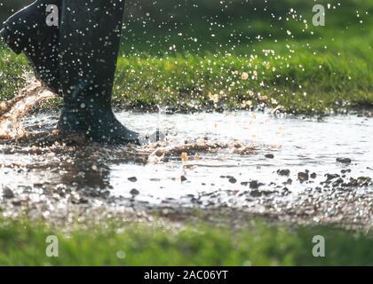 Person in grünen Gummistiefeln wandern in einem großen schlammigen Pfützen im frühen Morgenlicht kopieren Platz an der Seite des Bildes - Stockfoto
