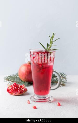 Granatapfel Weihnachten Cocktail mit Rosmarin, Champagner, club Soda auf grauem Beton Tabelle. Close Up.