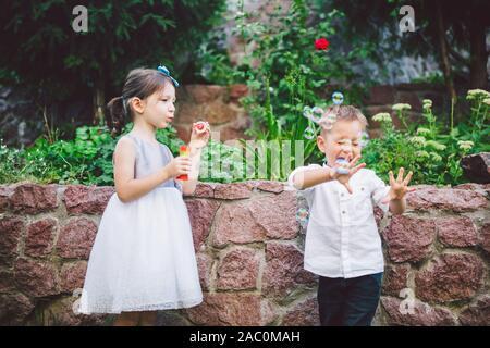 Zwei Kinder im Park bläst Seifenblasen und Spaß haben. Zwei Baby spielt mit Seifenblasen. Bruder und Schwester Spaß im Freien, glücklich - Stockfoto