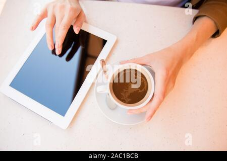 Blick von oben auf die Frau mit Tasse Kaffee im Cafe und die Arbeit mit Tablet - Stockfoto