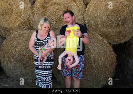 Porträt der britischen Familie auf Urlaub in die französische Landschaft, sitzen auf Strohballen. - Stockfoto
