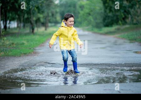 Ein nasses Kind springt in einer Pfütze. Spaß auf der Straße. Temperieren im Sommer. Spritzern, Tropfen Wasser, outdoor. wasserdichte Stiefel springen in Pfützen und Schlamm - Stockfoto