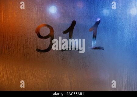 Das Wort 911 für United States not Service mit dem Finger auf nassen Glas mit verschwommen Lichter im Hintergrund geschrieben - Stockfoto