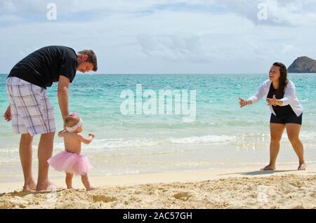 Eine Mutter und Vater die Förderung ihrer jungen Tochter am Ufer des Lanikai Beach, O'ahu zu gehen. - Stockfoto
