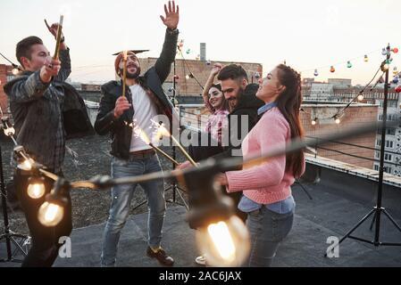 Schöne Menschen. Spielen mit Wunderkerzen auf dem Dach. Gruppe der jungen schönen Freunde