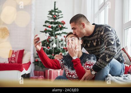 Emotionale Mädchen möchten lustiges Foto. Gerne jungen Menschen sitzt auf der Fensterbank im Zimmer mit Weihnachtsschmuck - Stockfoto