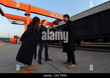 """(191201) - YIWU, Dez. 1, 2019 (Xinhua) - British merchant Taishan (C) fragt ein Mitarbeiter (R) über den China-Europe Güterzug Service Informationen in der Nähe von einen Zug für Europa in Yiwu West Railway Station in Yiwu gebunden, im Osten der chinesischen Provinz Zhejiang, Nov. 28, 2019. 2005, Nigel Cropp, ein britischer Mann, kam nach Yiwu kleiner Markt in der ostchinesischen Provinz Zhejiang Kaufleute zu unterrichten Englisch hier. Er nahm """"Taishan' wie sein chinesischer Name, weil er die Menschen schon immer den Eindruck, dass sie """"so stabil wie Mount Taishan'. Im Jahr 2008, er heiratete seine Schüler Wu Qinyan. In diesem Jahr, Tais - Stockfoto"""
