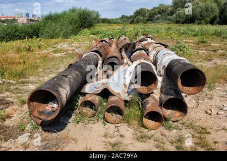 Haufen altes rostiges Metall Rohre links am Flussufer Feld - Stockfoto