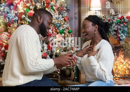 Liebende schwarze Kerl machen Vorschlag zu seiner Freundin zu Weihnachten - Stockfoto