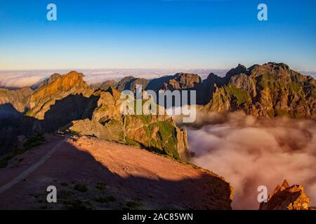 Natur Hintergrund mit Sonnenaufgang über den Wolken. Es liegt auf dem Gipfel des Pico do Arieiro Berg, Madeira, Portugal. Die Berge sind im Nebel verborgen - Stockfoto
