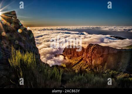 Natur Hintergrund mit Sonnenaufgang über den Wolken. Es liegt auf dem Gipfel des Pico do Arieiro Berg, Madeira, Portugal. Die aufgehende Sonne hat eine goldene Farbe. - Stockfoto