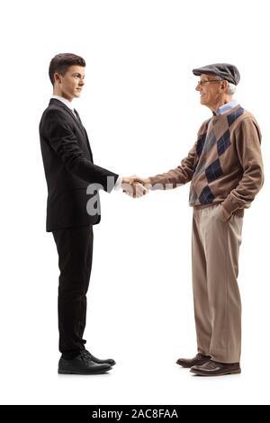Volle Länge Profil geschossen von einem jungen Mann in einem schwarzen Anzug Händeschütteln mit einem alten Mann auf weißem Hintergrund - Stockfoto